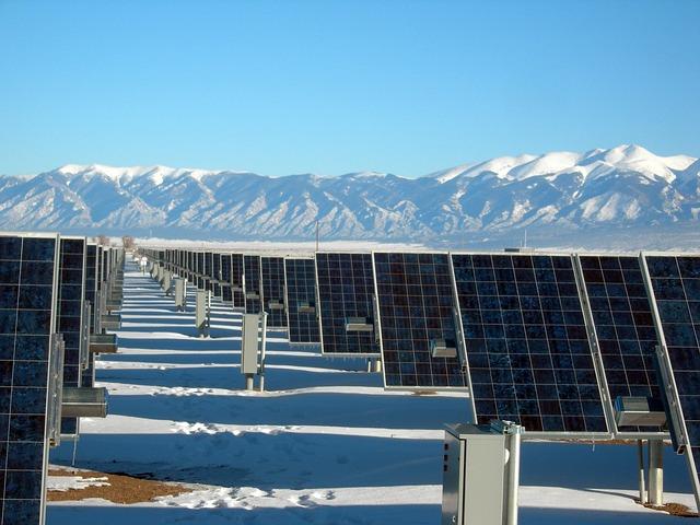Solar farm against mountain range.