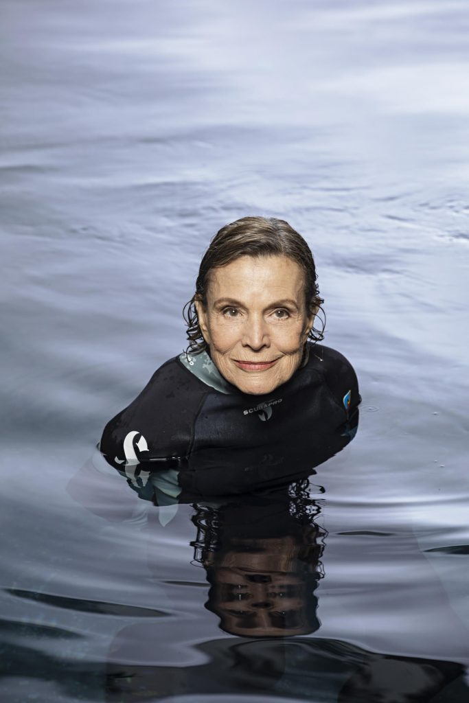 Sylvia Earle in wetsuit half submerged in water.